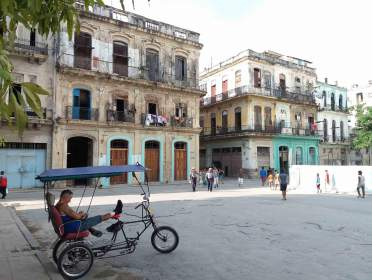 A bicycle taxi driver waits for customers at the Parque del Cristo in Havana